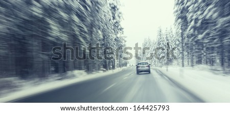 Danger and fast turndriving at the icy snow road. Motion blur visualizies the speed and dynamics. - stock photo