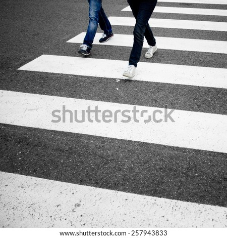 Danger artistic grain road crossing with pedestrians feet. Artistic grain filter effect used. - stock photo