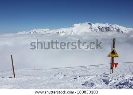 Danger avalanche sign in Alpe du Grand Serre ski resort, Isere, Alps, France, near Grenoble. - stock photo