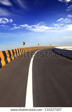 danger curve road sign with blue sky - stock photo
