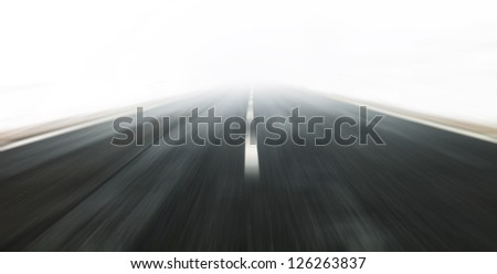 Danger fast driving at the heavy foggy road. Motion blur visualizies the high speed and dynamics. - stock photo