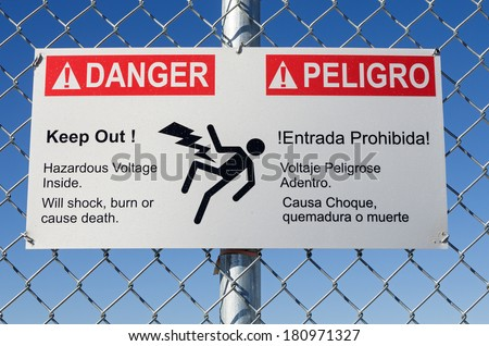 danger hazardous voltage keep out sign in English and Spanish on a fence with blue sky  - stock photo