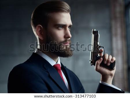 Danger man with gun looking aside portrait. - stock photo