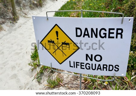 Danger No Lifeguards sign on the beach. - stock photo