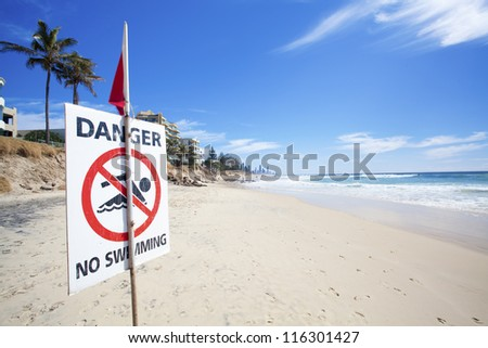 Danger no swimming sign on eroded Australian beach - stock photo