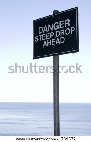 Danger sign at edge of the cliff - stock photo