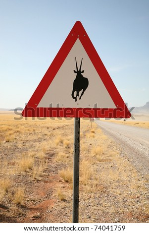 Danger Springbok Crossing Road Sign close to Country Road, Namibia, South West Africa - stock photo