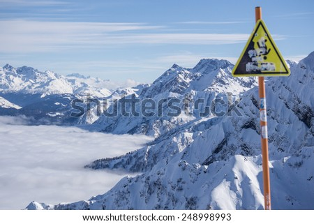 danger steep cliff mountain sign, mountains and blue sky above clouds, Krasnaya Polyana, Sochi, Russia - stock photo