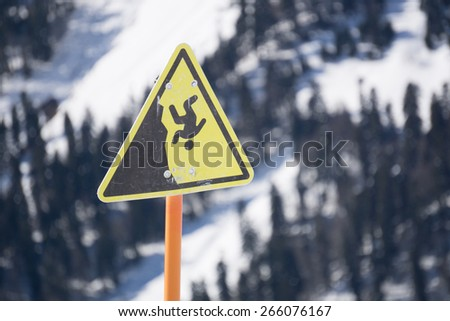 danger steep cliff mountain sign, mountains and cloudy sky - stock photo