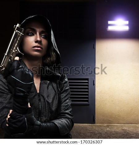 Danger woman with gun on night street. - stock photo