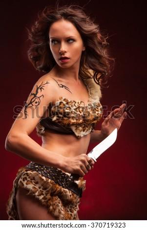 Dangerous beautiful woman with a knife. Warrior woman  - stock photo