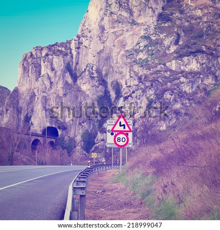 Dangerous Curves Sign at the Road Running Along the Railway in the Pyrenees, Instagram Effect - stock photo