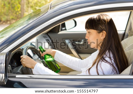 Dangerous driving with a drunk and inebriated female driver staring blearily at her steering wheel as she drives along holding a bottle of booze in her hand - stock photo