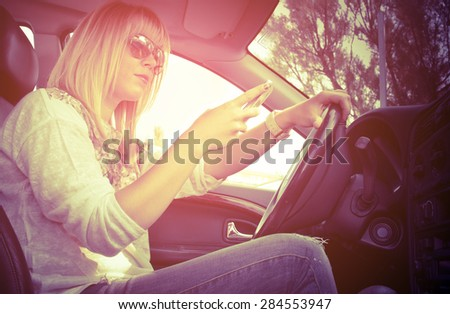 dangerous driving young lady sending text messages with phone on one hand and the other on steering wheel retro style filtered - stock photo