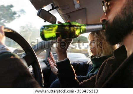 dangerous driving - young man drinking beer and driving car, while woman sees danger and  looks scared - drinking alcohol in vehicle and road accidents concept - focus on woman's hands gesture - stock photo