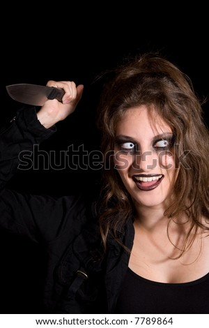 Dangerous looking woman with scary eyes and a knife in her hand - stock photo