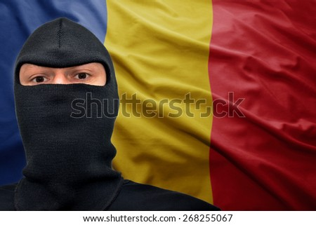 dangerous man in a mask on a romanian flag background - stock photo