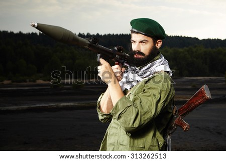 Dangerous man with AK-47 handgun and RPG bazooka  - stock photo