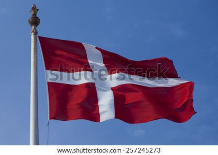 Danish flag flying against blue sky background - stock photo
