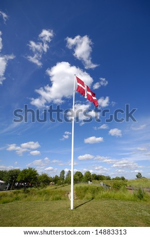 Danish flag, green nature, blues sky and clouds. - stock photo