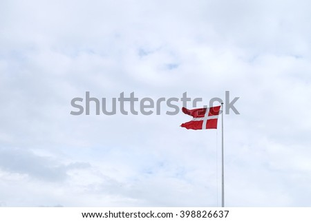 Danish flag waving in strong wind against cloudy sky Elsinore, Denmark - stock photo