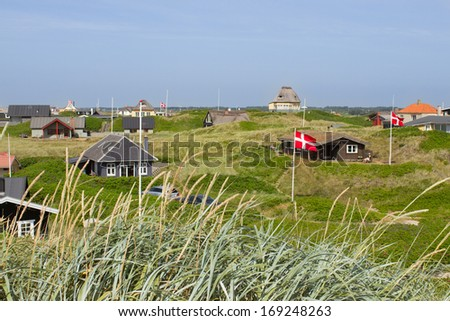 Danish holiday houses scattered among the sand dunes at the North Sea coastline in Soendervig, Denmark. Picture taken on a sunny summer day. Danish flags are visible on the picture. - stock photo