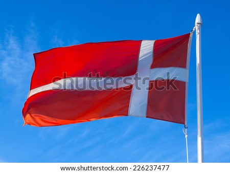 Dannebrog in flight against blue sky  - stock photo