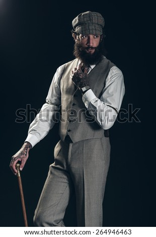 Dapper old-fashioned gentleman with a bushy beard wearing a cloth cap and waistcoat and carrying a cane over a dark background - stock photo
