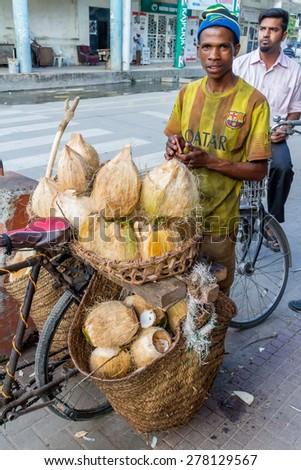 Dar Es Salaam: April 21: A local vendor sells Coconuts on the streets of downtown Dar Es Salaam on April 21, 2015 in Dar Es Salaam, Tanzania - stock photo