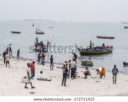 DAR ES SALAAM, TANZANIA - JANUARY 15, 2015: Local people go out fishing on small boats in the port area of Dar es Salaam, Tanzania, East Africa, on a weekend. Horizontal orientation.  - stock photo