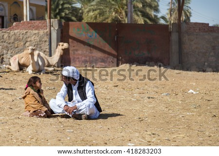 DARAW, EGYPT - FEBRUARY 6, 2016: Local camel salesmen and little girl sitting on the ground at camel market. - stock photo