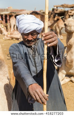 DARAW, EGYPT - FEBRUARY 6, 2016: Portrait of elderly camel salesman with stick at Camel market. - stock photo