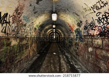 Dark and long undergorund passage with light - stock photo