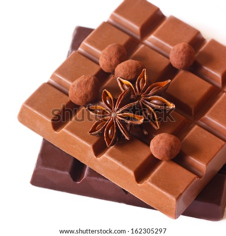 Dark and milk chocolate bars with anise and praline on white. - stock photo
