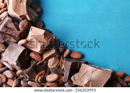 Dark and milk chocolate pieces and cocoa beans on color wooden background - stock photo