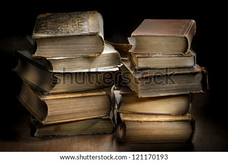 Dark and moody photograph od two stacks of old worn antique books. - stock photo