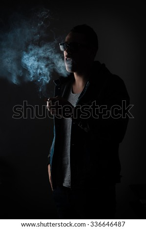 Dark and sullen shot of a young man smoking over a black background. - stock photo