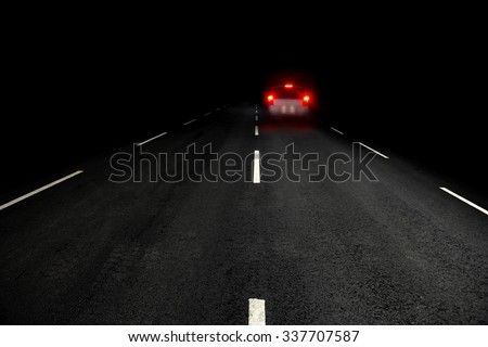 Dark asphalt road and car with red rear lights - stock photo