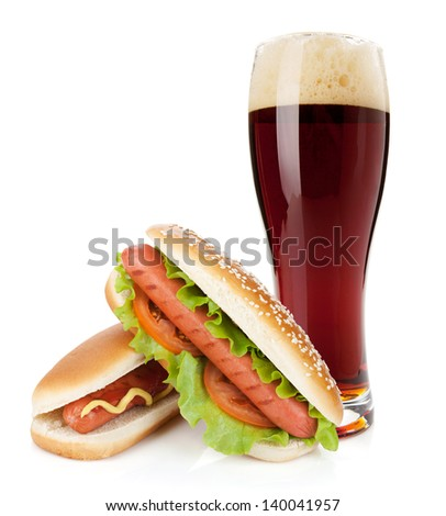 Dark beer glass and two hot dogs with various ingredients. Isolated on white background - stock photo