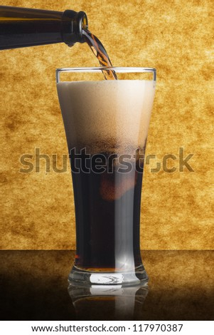 Dark beer pour from bottle to glass on beautiful background - stock photo