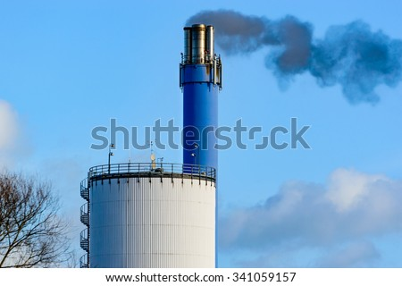 Dark, black smoke is coming out of a blue chimney. Some kind of silo or storage building is seen in front. Blue sky in background. Some clouds drift by. - stock photo