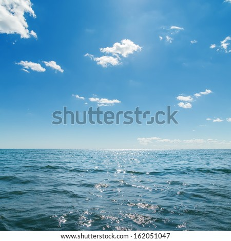 dark blue sea and deep blue sky with clouds - stock photo