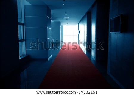 Dark blue tone of long hall with red carpet. - stock photo