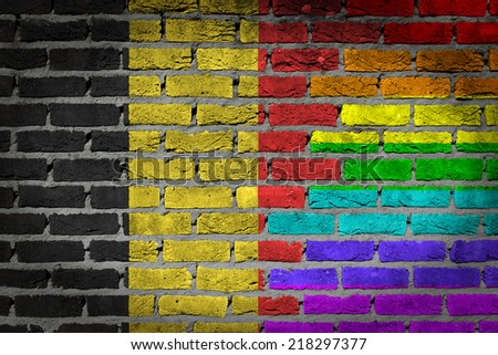 Dark brick wall texture - country flag and rainbow flag painted on wall - Belgium - stock photo