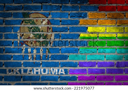 Dark brick wall texture - coutry flag and rainbow flag painted on wall - Oklahoma - stock photo