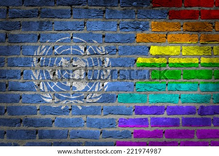 Dark brick wall texture - coutry flag and rainbow flag painted on wall - United Nations - stock photo
