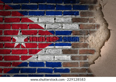Dark brick wall texture with plaster - flag painted on wall - Cuba - stock photo