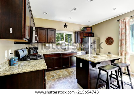 Dark brown cabinets with granite tops. Kitchen island with stools - stock photo