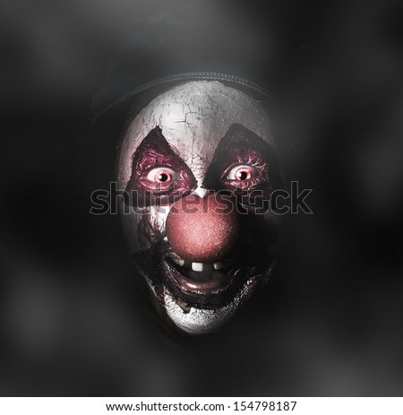 Dark carnival portrait on the face of an evil clown with a scary joker smile laughing in the black darkness. The Bogyman - stock photo