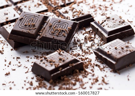 Dark chocolate bar and its broken pieces and some powder around over a white background - stock photo